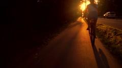 Slim brunette girl riding a bike along summer sunset road. Slow motion tracking Stock Footage