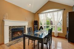 American dining room interior with black table set and fireplace. Vaulted cei Stock Photos