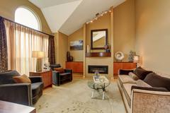 Beautiful brown and beige living room with vaulted ceiling. Furnished with ni Stock Photos