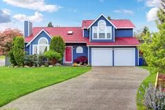 Beautiful curb appeal with blue exterior paint and red roof. Nice front lands Stock Photos