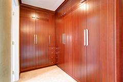 Luxury wardrobe room with brown modern built-in cabinets and carpet floor Stock Photos