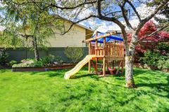 View of kids playground in green backyard garden with birch trees and flower  - stock photo