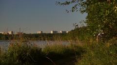 Beautiful brunette girl riding a bike along summer riverside. Slow motion shot Stock Footage