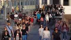 People walk, sit relaxing, have fun talking, stroll along footbridge in warm day Stock Footage