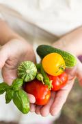 Person holding freshly picked locally grown veggies. - stock photo