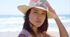 Smiling young woman holding her sunhat Stock Footage