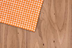 Rustic wooden boards with a orange checkered tablecloth Stock Photos