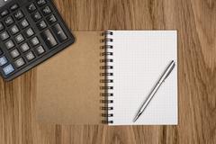 Notebook, ballpen and calculator on wooden desk Stock Photos