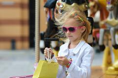 Child On Carousel with full shopping bags. Stock Photos