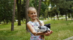 Pigeons sit on the girl's hand and peck feed Stock Footage