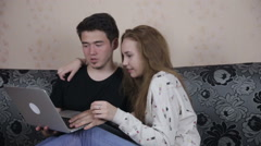 Home, technology and relationships concept - handsome couple with laptop - stock footage