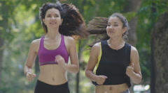 Two attractive Fitness athletic young women with curly hair running in the park - stock footage