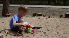 A boy plays in the sandbox Stock Footage