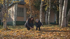 Mom with her son sorted out the yellowed leaves. Stock Footage