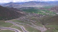 EPIC SCENERY OF BEAUTIFUL MOUNTAINS & WINDY TWISTING MOUNTAIN ROAD IN TIBET Stock Footage