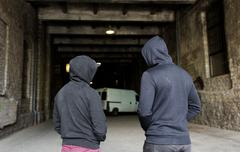 Addict men or criminals in hoodies on street Stock Photos