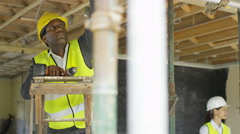 4K Builders working at construction site with architects or engineers overseeing Stock Footage