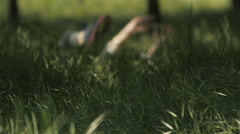 Girl swinging legs laying in the grass and appear only hands with the phone Stock Footage