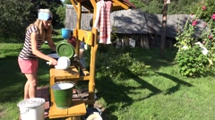 Manual hand laundry wash in bowl by poor peasant woman in farm house yard. 4K Stock Footage