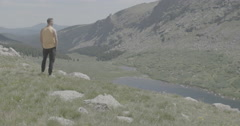 Hiker looking over lake wide shot Stock Footage