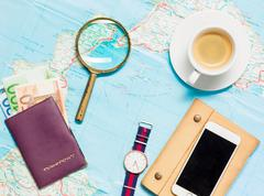 Preparation for travel concept - map, magnifying glass, cup of coffee, notepad - stock photo