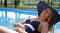Woman sunbathes near the swimming pool Stock Footage