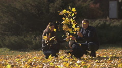 Young family indulges in a park in autumn. Stock Footage