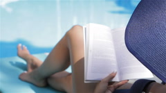 Woman turns the page of book near the swimming pool Stock Footage