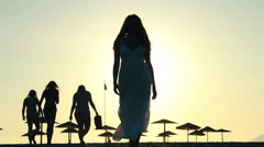 Sunset on the beach / Silhouette of young woman in a long dress walking - stock footage