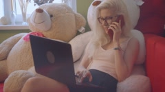 Blonde playing and working on laptop and talking on phone Stock Footage