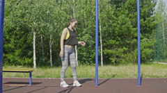 Sport Girl is training on the pole in the park - stock footage