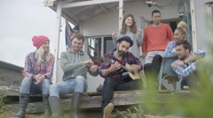 4K Happy group of friends hanging out at beach house, playing guitar & singing.  Stock Footage