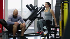 Man giving bottle of fresh drinking water to woman during active workout in gym Stock Footage