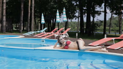 Long shot of woman lying on the pool edge Stock Footage