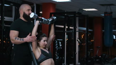 Male coach helping young woman with dumbbell exercise during workout in gym Stock Footage