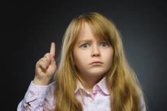 Portrait of displeased angry girl with threatens finger isolated on gray Stock Photos