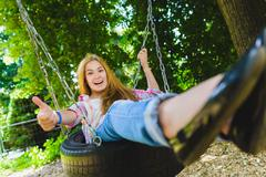 Little girl at playground. Child playing outdoors in summer. Teenager on a swing Stock Photos