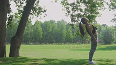 Work-out: Young attractive fitness Woman doing acrobatic element in the park at Stock Footage