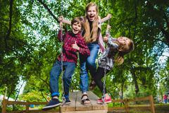 Smiling kids having fun at playground. Children playing outdoors in summer Stock Photos