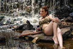 Sexy woman archer lying on rocks Stock Photos