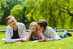Smiling kids having fun at grass. Children playing outdoors in summer. teenagers Stock Photos