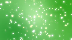 Sparkly  particles moving across a green gradient background Stock Footage