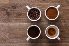 Four cups of coffee, phases of drink - bean, ground and empty cup. Stock Photos