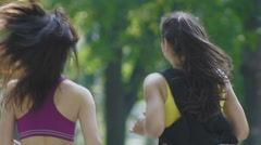 Two attractive Fitness athletic young women with curly hair dressed in sport Stock Footage