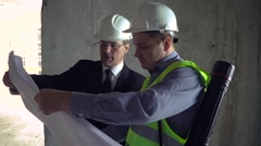 Architect and foreman looking at development plan - stock footage