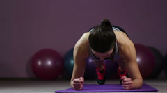 Young woman taking front hold position, working hard in gym to have fit body Stock Footage