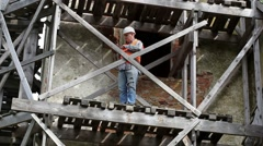 Construction worker standing on wooden scaffolding and using tablet PC Stock Footage