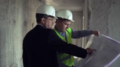 Architect and foreman discussing construction plan - stock footage