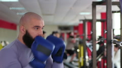 Strong male boxer sparring with punch bag, active sportsman practicing in gym Stock Footage