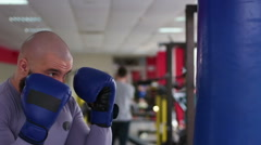 Professional male boxer practicing punches on boxing bag, working hard in gym Stock Footage